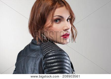Seductive female look. Stylish life. Beautiful young woman portrait closeup. Grey background, fashion concept