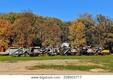 Old threshing machines are lined up along a grove of autumn colored trees