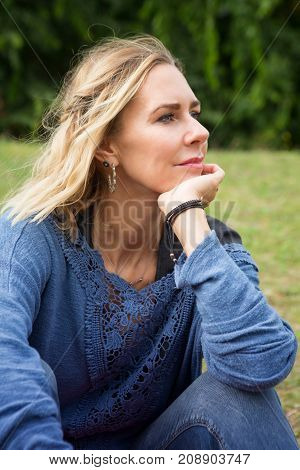 portrait of blond woman sitting outside in the park