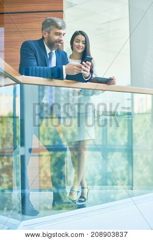 Smiling mixed race businesswoman and her handsome bearded colleague watching funny video on smartphone while standing at spacious office lobby and waiting for conference beginning