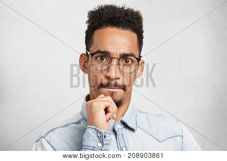 Portrait Of Mixed Race Serious Focused Bearded Man With Afro Hairstyle, Keeps Hand On Chin, Pressses