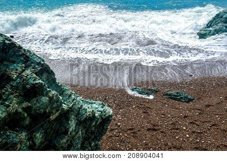 The sea view. Waves and shore and large stones of green color. Montenegro