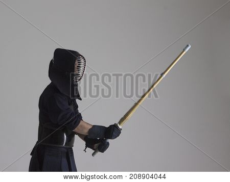 Portrait of man kendo fighter with bamboo sword. Shot in studio