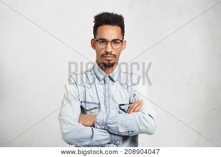 Portrait Of Serious Male Boss Has Grumpy Expression, Being Annoyed With Workers, Keeps Arms Folded,