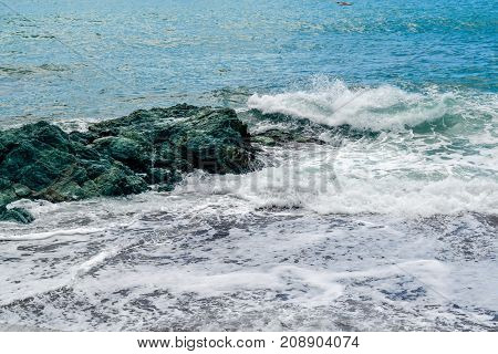 The sea waves break against a large green stone.