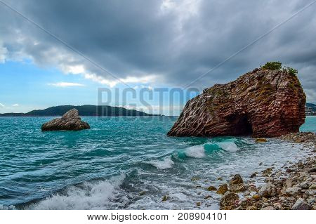The waves break against the stony shore. The sky is covered with low clouds. Stone islands. Montenegro