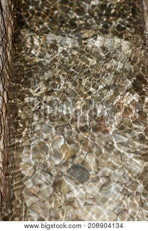 Reflections in transparent water with different pebbles on the bottom