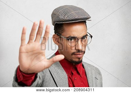 Serious Dark Skinned Male Makes Stop Gesture With Palm, Says No, Expresses Denial Or Restriction. At
