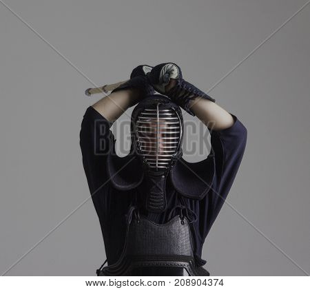 Man is practicing kendo in traditional armor .He swinging with bamboo sword .Studio shot