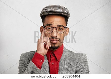 Portrait Of Thoughtful Pensive Mixed Race Male Employee Wears Trendy Cap, Red Shirt And Jacket, Has