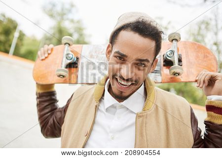Portrait Of Positive Young Teenager Practices Riding Skateboard Outdoors, Has Happy Expression As Ac
