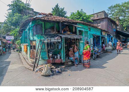 KUMARTULI KOLKATA INDIA - OCTOBER 10 2014 : Two men and one woman gossiping - street scene of Kolkata.