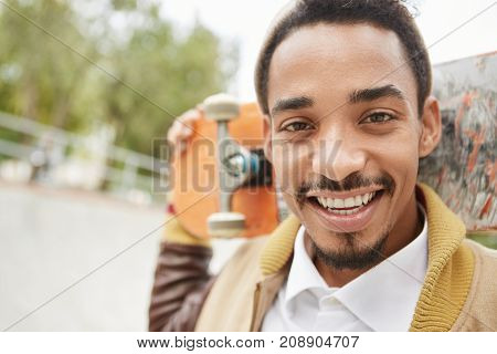 Outdoor Portrait Of Handsome Man With Dark Eyes, Beard And Mustache, Keeps Skateboard Behind Head, F