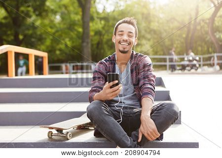 Joyful Restful Mixed Race Teenager Sits On Ground Outdoors, Uses Mobile Phone As Listens Melodies Wi
