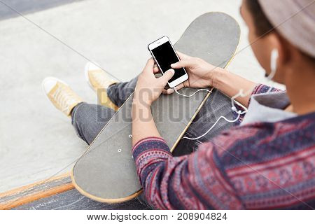 Back View Of Hipster Teenage Boy Rests On Skate Park, Skateboards With Friends, Holds Smart Phone Wi