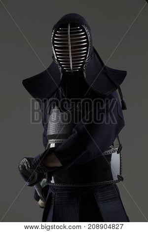 portrait of male in tradition kendo armor with bamboo sword preparing for the fight. shot in studio on grey background