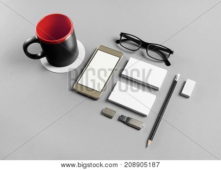 Photo of blank stationery and smartphone set on gray paper background. Branding template. Objects for placing your design.