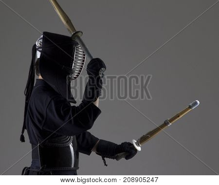 Man is practicing kendo in traditional armor .He swinging with two bamboo swords .Studio shot