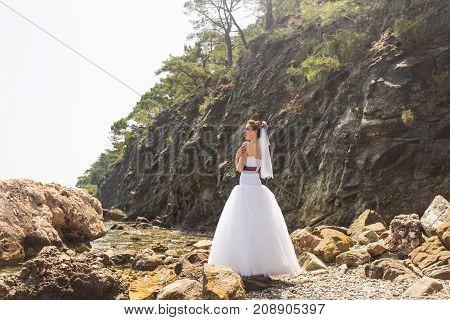 Beautiful young bride. Wind lifting long bridal veil.