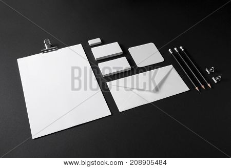 Photo of blank stationery set on black paper background. Mock up for branding identity. ID template.