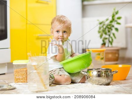 Kid toddler boy sitting on the kitchen floor and playing with flour.