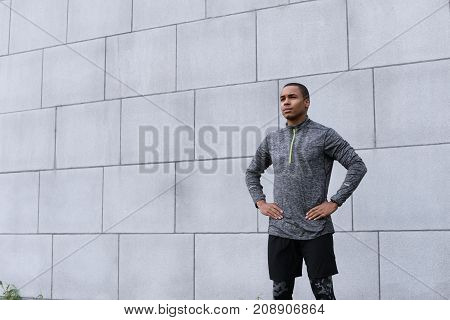 Isolated cropped shot of attractive young Afro American sportsman in trendy sports clothes standing at grey brick wall keeping hands on his waist while relaxing after running exercise feeling tired