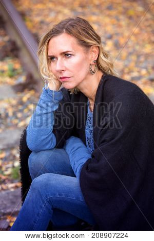 blond woman sitting outside on trail tracks and looking sad