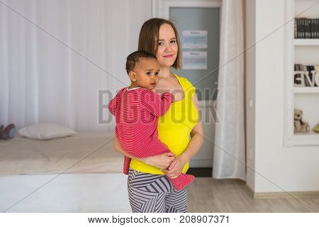 Smiling Mother Playing With Baby Son At Home