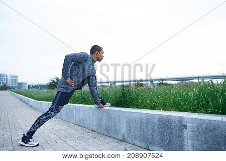 Candid lifestyle shot of muscular strong African American male in trendy outfit stretching legs outdoors warming up mucles before cardio training. Virality physical exercise workout and motivation