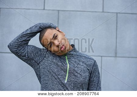 Sports and warm up activity concept. Serious fit young dark-skinned man wearing sports fleece jacket warming up before high intensity cardio training stretching neck muscles at grey brick wall