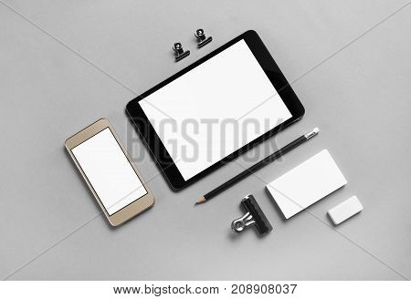 Gadgets with blank screens and stationery on gray paper background. Template for placing your design. Top view.