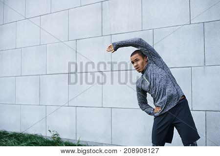 Isolated outdoor portrait of confident young dark-skinned sportsman in stylish outfit bending sideways doing stretching and warm up exercises preparing his mucles for workout. Sports and motivation