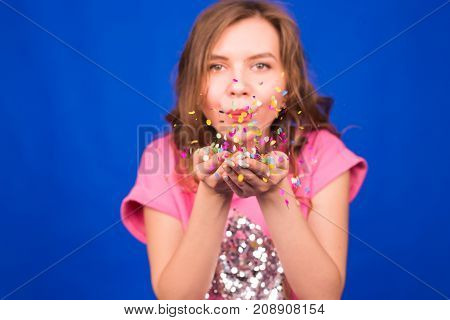 Portrait of beautiful woman blowing confetti in the air, party new years eve celebration on blue background.
