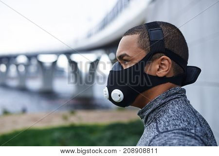 Profile picture of self-determined confident young African athlete wearing black training mask to increase load on breathing muscles during morning cardio workout routine outdoors. Sports and fitness