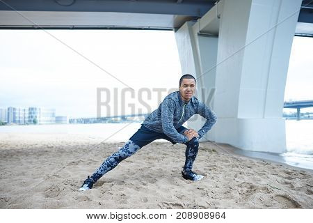 Lifestyle picture of attractive young African man in fashionable training clothes doing side lunges outdoors standing on sandy beach under bridge during morning workout. Wellness health and sports