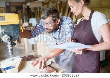 Portrait of two carpenters, man and woman, operating drilling machine making furniture in woodworking shop
