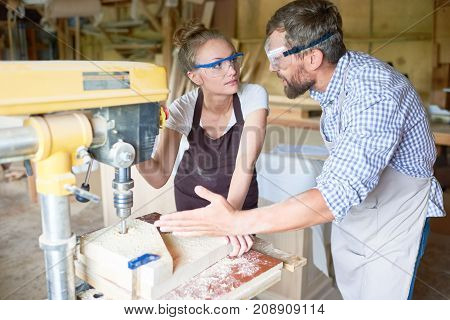 Portrait of bearded carpenter teaching his female assistant operating drilling machine  in woodworking shop