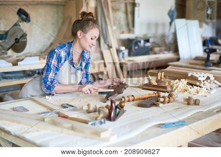Portrait of joyful female carpenter polishing wooden part in modern workshop, copy space
