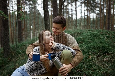 Lovely cute couple of teenagers in love enjoying each other's company spending weekends outdoors in wild nature hugging and warming up themselves drinking hot tea or coffee out of themal mugs