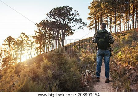 Rearview of a young African man wearing a backpack standing on a trail while hiking alone in the hills on a sunny day