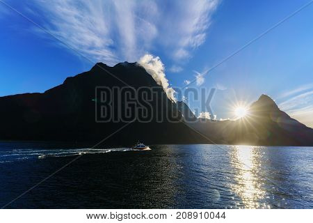 Tour cruise in Fiordland National Park in Milford Sound / Piopiotahi Marine Reserve viewing beautiful sunset and silhouette Mitre Peak South Island of New Zealand