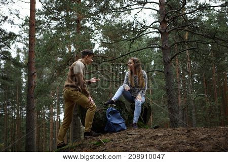 Hiking traveling people tourism vacations and active lifestyle concept. Cute teenage sitting on stump in forest and smiling while listening to charismatic guy who is telling something to her