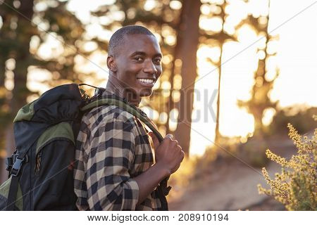 Portrait of a smiling young African man wearing a backpack standing on a trail while hiking alone in the late afternoon