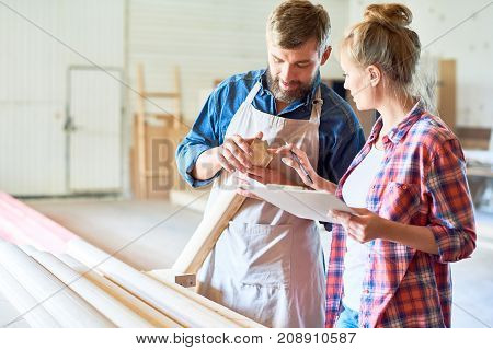 Portrait of two carpenters, man and woman, evaluating quality of wood in workshop studio, choosing best materials, copy space