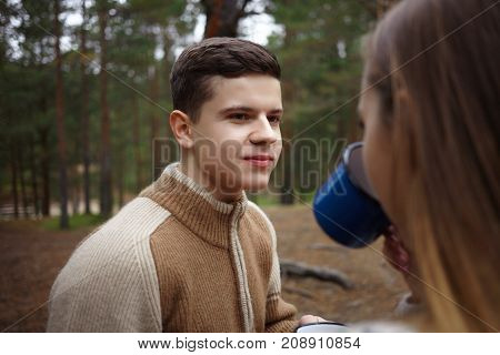 Close up portrait of handsome young brunette man in warm sweater posing against green pine trees background and looking at unrecognizable girl who drinking tea and sitting with her back to camera