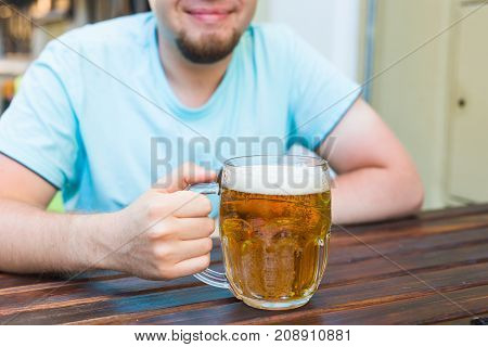 Hand holding a glass of beer on wooden table.