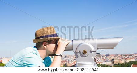 tourist man looks through the long binocular landscape