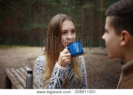 Cute teenagers having rest and drinking hot beverage in park or at camp in forest: pretty girl with long hair enjoying warm tea and looking at her boyfriend with smile. Happy couple of hikers in woods