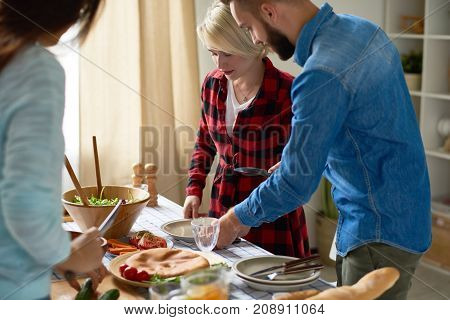 Group of young people preparing dinner for festive celebration standing at big table setting up together