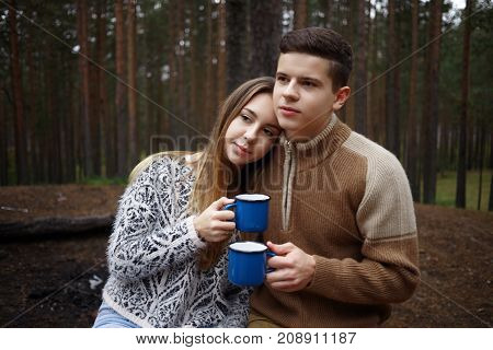 Cozy shot of romantic loving couple hugging and holding blue mugs with hot drink enjoying peaceful morning in forest or park looking happy and carefree. People love tourism and active lifestyle
